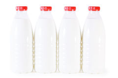 Four bottles of milk with red cap isolated Stock Images