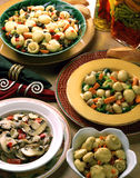 Four bowls of marinated mushrooms. Four bowls of marinated mushrooms on beautifully set table with napkins, bread and bottles of oil and vegetables Stock Images