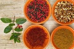 Four bowls with saffron, pepper, ras en  hanout, fresh mint Stock Image
