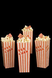 Four Boxes of Popcorn With Movie Tickets. Vertical shot of four full boxes of popcorn with movie tickets stuck in them on a black background Stock Photos