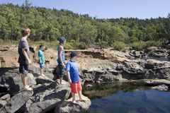 Four Boys Exploring the South West of Australia. Four boys standing on the shore of a rocky river in Western Australia, exploring the surroundings stock photo