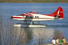 Four Boys Watching Taxying Seaplane, Yellowknife. Royalty Free Stock Photos