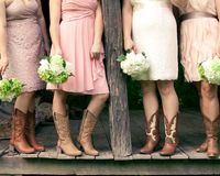 Bridesmaids in cowboy boots on a rustic porch. Four bridesmaids with bouquets and wearing cowboy boots at a country themed wedding royalty free stock image