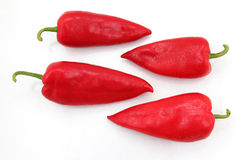 Four bright red sweet peppers on a white background