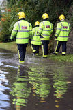 Four British firemen. Walking beside a flood with reflections Stock Photography