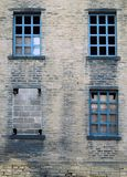 Four broken and bricked up windows in a derelict abandoned house Stock Photography