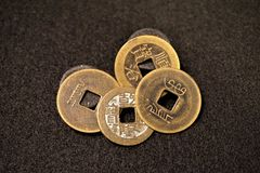 Square hole Chinese cash coins. Four bronze and copper antique 17th century pieces display Manchurian and Chinese characters. Emperor Shunzhi cast molds of model stock photos