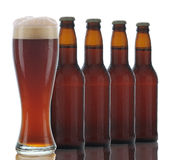 Four Brown Beer Bottles and Full Glass Stock Image