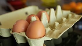 Four brown chicken eggs in a cardboard box for ten eggs. Four brown chicken eggs in a cardboard box for ten eggs. High quality 4k footage stock footage