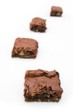 Four brownies on a white background. Four fresh homemade chocolate brownies on a white background Royalty Free Stock Photography