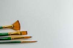 Four brushes on paper Royalty Free Stock Photos