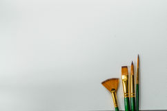 Four brushes on paper Royalty Free Stock Photography