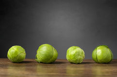 Four brussels sprouts on a row. Four brussels sprouts on raw on wooden table Royalty Free Stock Photography