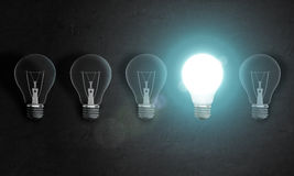 Four bulbs in row on concrete wall, one of them is very bright. Idea concept Royalty Free Stock Images