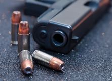 Four bullets with a black pistol. Four hollow point 9mm bullets with a black pistol Royalty Free Stock Images