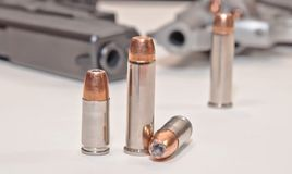 Two sets of different bullets with a revolver and a pistol in the background. Four bullets, two 9mm and two .357 magnum with a stainless .357 revolver and a royalty free stock photos