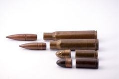 Four bullets. White background rifle and gun Royalty Free Stock Photos