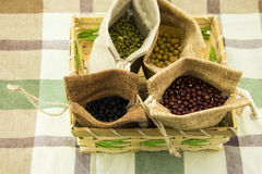Four burlap sacks and yellow beans, black beans, r Royalty Free Stock Photo
