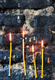 Four burning candles on old sooty blackened stone wall Stock Image