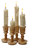 Four burning candles in wooden candlesticks Stock Photos