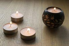 Four burning candles. On wooden floor closeup Stock Photos