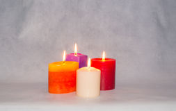 Four burning colored candles Stock Images