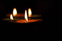 Four burning colorful candles indian style for Diwali celebration on black background. Vertical