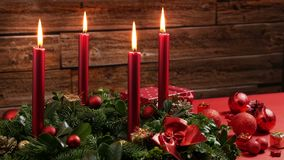 Four burning red candles on a traditional advent wreath with festive decoration