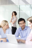 Four business colleagues holding a meeting, one talking on mobile phone Royalty Free Stock Images