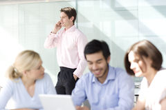 Four business colleagues holding a meeting, one talking on a mobile phone Royalty Free Stock Image