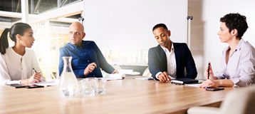 Four business executives collaberating on a new project together Stock Photography