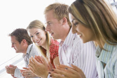 Four business people applauding indoors smiling stock photos