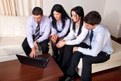 Four business people on couch using laptop Stock Image
