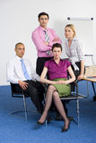 Four business people posing in boardroom, smiling, portrait Royalty Free Stock Image