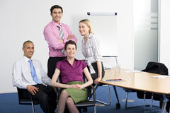 Four business people posing in boardroom, smiling, portrait Stock Image