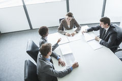 Four business people sitting around a table and having a business meeting, high angle view Royalty Free Stock Photography