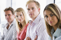 Four business people sitting indoors smiling Stock Photography