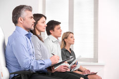 Four business people sitting in a row on conference. Taking notes and listening with attention stock photos