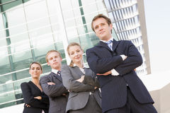 Four business people standing outdoors smiling Stock Photo