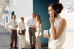 Four business people talking in corridor outside meeting room, focus on businesswoman using mobile phone, smiling Royalty Free Stock Images