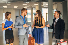 Four business people talking in office lobby Royalty Free Stock Photos