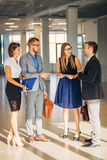 Four business people talking in office lobby Stock Photo