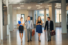Four business people talking and walking in office lobby Royalty Free Stock Photo