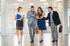 Four business people talking and walking in office lobby Royalty Free Stock Photography