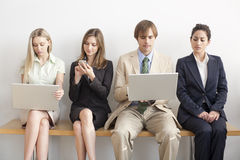 Four Business persons. Four businesspersons sitting on bench working on laptops and cellphones. Horizontally framed shot Royalty Free Stock Photo