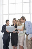 Four Business persons. Four businesspersons with paperwork. Horizontally framed shot Stock Photos