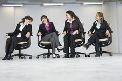 Four business women seated in a line and laughing.