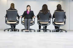Four business women sitting in office chairs. Four business women sitting on office chairs. One person opposed to others royalty free stock photos