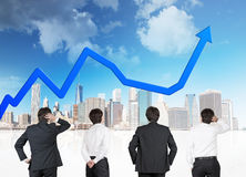 Four businessman looking at blue arrow Stock Photo