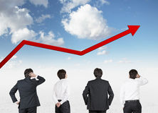 Four businessman looking to arrow Stock Images